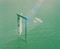 緑の水面上の白い扉を過ぎる紙飛行機