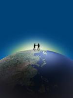 地球儀上で握手するビジネスマン