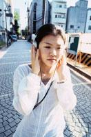 ヘッドホンを聴きながら歩く日本人の女の子