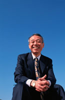 土手に座る笑顔の中高年ビジネスマン