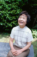 庭で腰掛ける60代女性のポートレイト