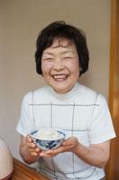 茶碗によそったご飯を差し出す60代女性