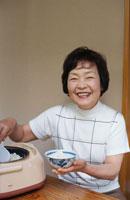 茶碗にご飯をよそっている60代女性