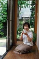縁側でお茶を飲んでいる60代女性