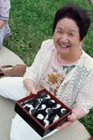 公園でピクニックをしているシニア女性