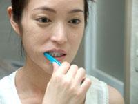洗面台で歯磨きをする女性