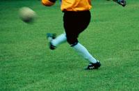 サッカーボールを蹴る男性選手