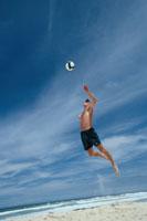 ビーチバレーボールのサーブをする外国人男性 ゴールドコースト