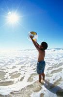 ビーチで地球儀を持つ日本人の少年