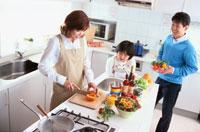 キッチンで野菜を切る母とそれを眺める父と娘