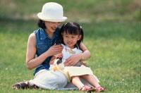 芝生に座る日本人の女の子と母親とウサギ