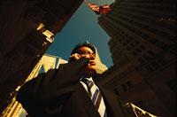 携帯電話で話す日本人ビジネスマンと高層ビル群