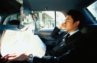 車内で携帯電話で話す日本人ビジネスマン