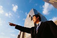 指さす日本人ビジネスマンと高層ビル