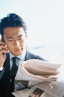 新聞を読む日本人ビジネスマン