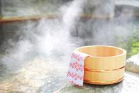 湯気立つ露天風呂とヒノキ桶