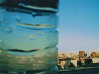 街並みと水滴のついたペットボトル