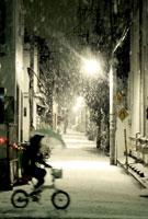 雪の中を傘をさして自転車に乗る人