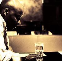 グラスを見つめる黒人男性