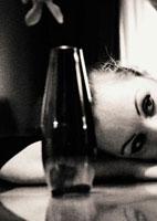 テーブルにもたれる外国の女性とボトル瓶