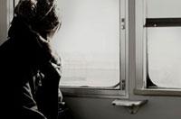 電車の窓の外を見る女性