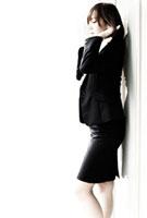 壁にもたれるスーツを着た女性