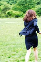 スーツを着て草原を走る女性