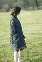 草原で後ろ向きにたたずむ女性
