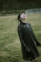 草原で空を見る女性
