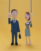 つり革につかまる男性と女性