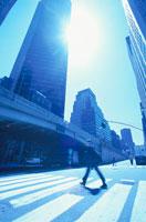 横断歩道を渡る人物と太陽の光(青)