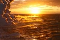 日の出に輝く蒸気噴煙と海