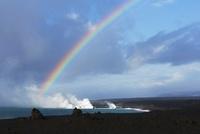 海上を漂う蒸気噴煙と溶岩台地に現れた虹