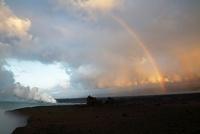 早朝朝焼けの溶岩台地に架かる虹と蒸気噴煙