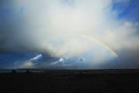 早朝の溶岩台地に現れた虹と雲と海
