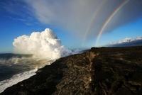 蒸気噴煙と溶岩台地に架かるダブルレインボーと海