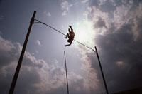 棒高跳びでジャンプする人のシルエット