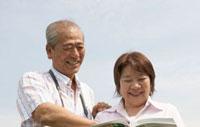図鑑を見るシニア夫婦