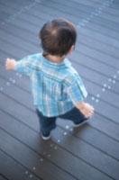 ボードウォークを歩く後姿の日本人の男の子の赤ちゃん