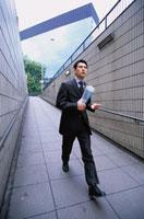 大股で通路を歩くビジネスマン