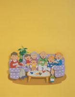ソファに座ってお茶をする家族