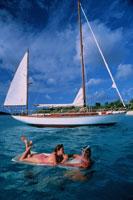 ビーチマットで遊ぶ外国人カップルとヨット ヴァージン諸島