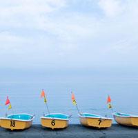朝の砂浜に並ぶボート