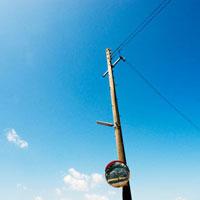 カーブミラーの在る電柱と青空