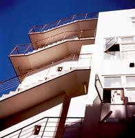 午後の日を浴びる白いビルの階段