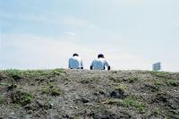 運動公園の土手に座る二人の高校野球部員