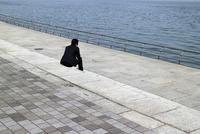 海を眺める黒い背広を着たサラリーマン