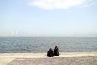 海岸公園の階段ベンチから海を眺めるふたリ連れのわかい女性