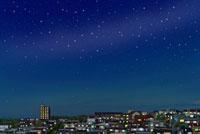 住宅の密集した丘の夜景と広がる星空