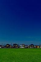 草原と窓明かりが点いた夜の住宅地